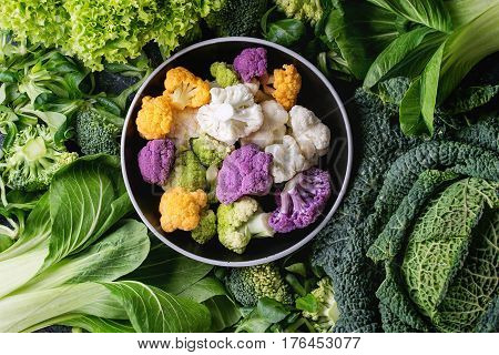 Variety of raw green vegetables salads, lettuce, bok choy, corn, broccoli, savoy cabbage round colorful young cauliflower in black bowl. Food background. Top view