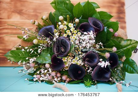 A bouquet of dark noble cal with frosted flower.