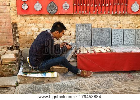 KATHMANDU, NEPAL - NOVEMBER 13, 2016: Nepalese stone carver working at the Swayambhunath temple in Nepal.