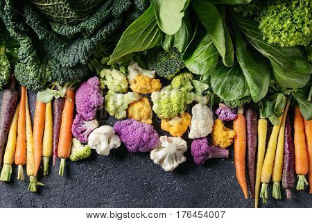 Variety of raw green vegetables salads, lettuce, bok choy, corn, broccoli, savoy cabbage, colorful young carrots and cauliflower over black stone texture background. Top view, space for text
