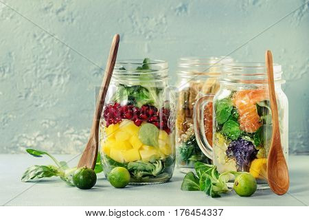 Variety of salads in mason jars. Fruit salad mango, pomegranate, greens, vegetables pasta, carrots, cauliflower, salmon. Standing with mini limes and wood spoon over blue background. Food to go.