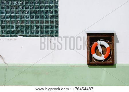 life preserver attached to a white and greenwall