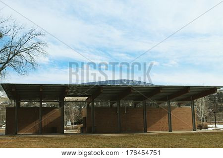 Closeup of outdoor stage with overhanging roof brick walls and beams. Tree branches and grass field in foreground. Hill and blue sky with white cloud background.