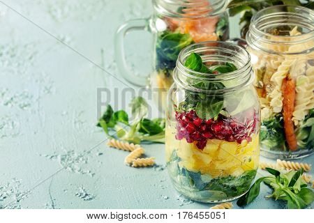 Variety of salads in mason jars. Fruit salad mango, pomegranate, greens, vegetables, wholegrain pasta, carrots and cauliflower, salmon. Standing over blue texture background. Food to go.