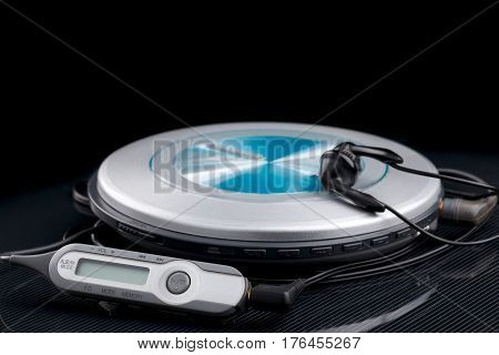 personal cd player with remote control and portable audio earphones on black background