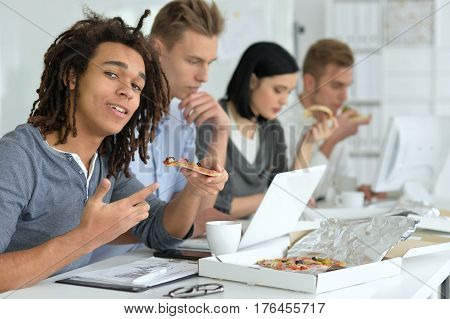 Portrait of colleagues having a break time at office eating pizza