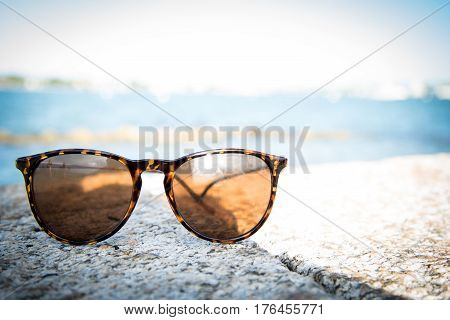 Sunglasses on a ledge with the atlantic ocean blurred background in St. Augustine Florida