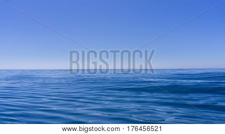 Abstract background deep blue oily looking surface of ocean in motion defocused with hazy sea shimmer and sky on horizon