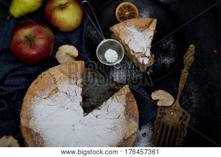 Homemade apple pie. Apple pie tart, ingredients - apples and cinnamon on rustic wooden background