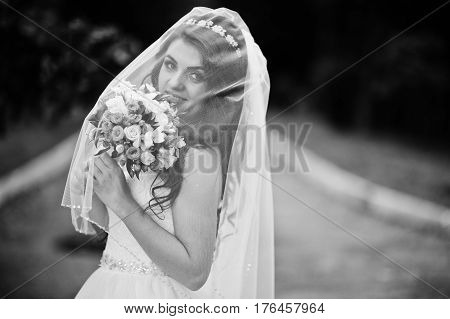 Charming Brunette Bride Under Veil With Bouquet At Park. Black And White Photo