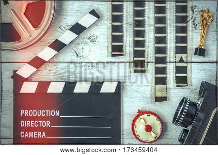 Clapperboard reel film and an old movie camera lie on a painted wooden table