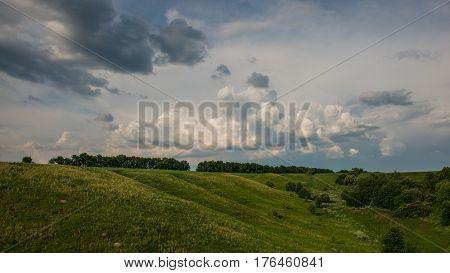 Rural landscape in hilly terrain with rain clouds. Ukraine. Europe.