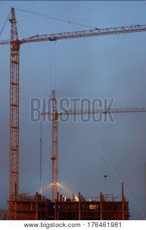 Two cranes on the construction site, unfinished house, foggy evening twilight, building lighting.