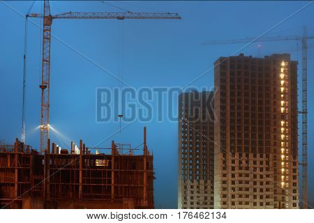 Cranes on a large construction site, unfinished multi-storey houses, foggy evening twilight.