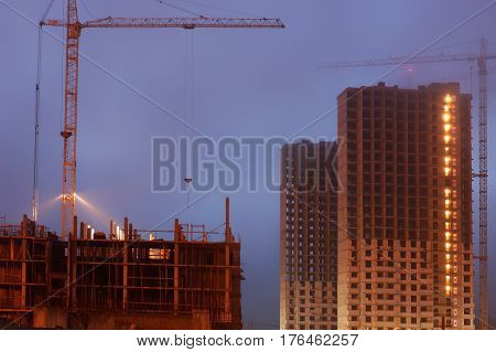 Construction crane on the site, unfinished multi-storey houses, fog covers the upper floors, evening twilight.