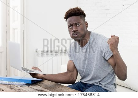 young attractive african american man sitting at home living room working with laptop computer and paperwork looking stressed and desperate maybe studying for exam in education concept
