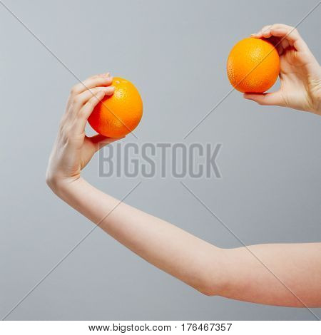 Chinese Orange on Asian woman hand on gray concrete background.