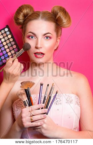 Younge attractive blonde woman with colorful make up with cosmetic brushes and shadows in her and make up master's hands