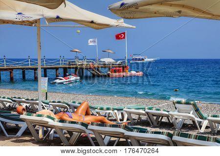 Antalya Turkey - 29 august 2014: Young woman takes a sun bath lying in a beach sunbed on a deserted beach.