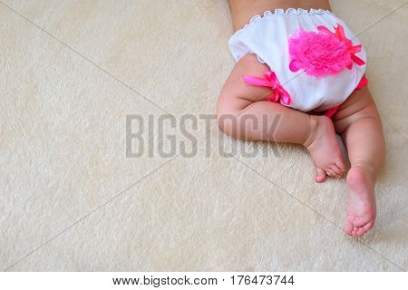 baby in little white panties lying on a homogeneous background