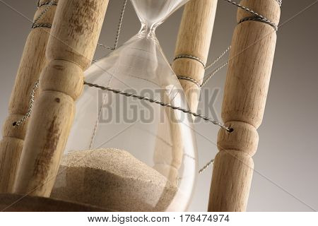Close up vintage hourglass against gray background