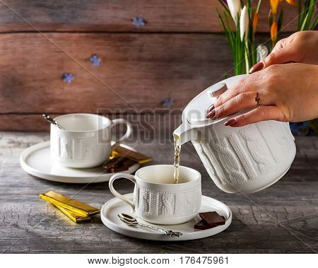 White Cup of tea. The tea party. Chocolate on the saucer. Pour tea. Pot of flowers in the background. Selective focus. Wooden background