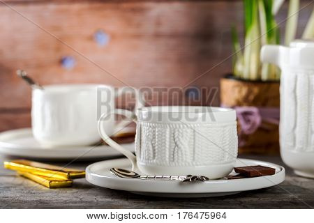 White Cup of tea. The tea party. Chocolate on the saucer. Selective focus. Wooden background