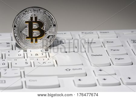 Shining silver and gold metal BTC bitcoin coin on white computer keyboard.
