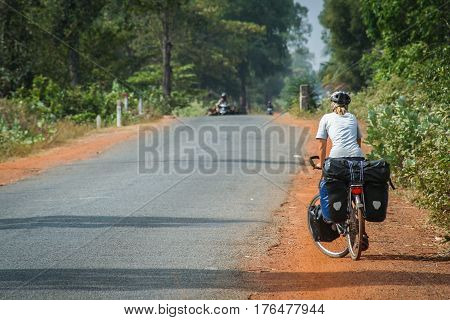 Woman on a cycle touring trip in rural part of Cambodia