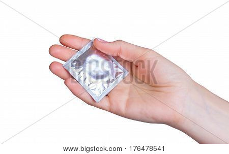 Hand holding a condom on a white background isolated