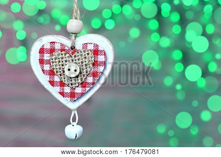 Christmas decoration: Wooden heart with jingle bell against green Christmas lights