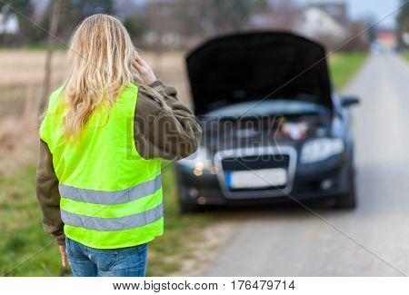 a woman with reflective vest stands on a broken car