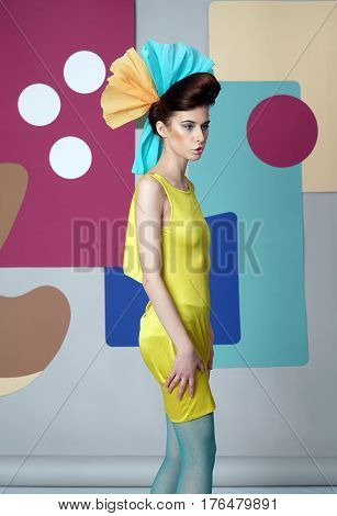 Profile of attractive girl in bright eccentric outfit. Woman dressed in short dress with open shoulders and paper headdress. She looks to side, mouth closed. Color background: circles, rectangles