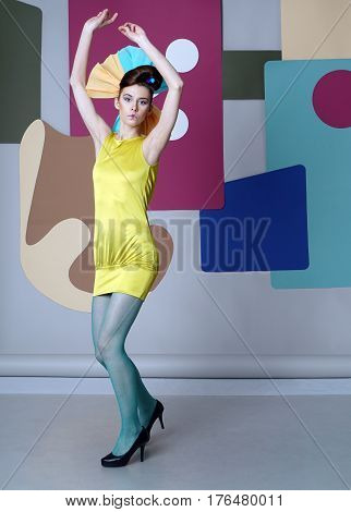 Girl in eccentric dress dancing on the color background. Danish design. She dressed in short yellow dress and green tights, hands over head. Backdrop: circles, rectangles, Egg chair.