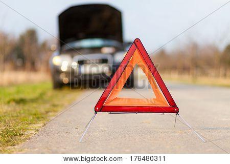 breakdown triangle stands near a broken car