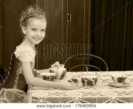 Beautiful little girl Princess , sitting at an antique table with a lace tablecloth and drinking tea. Black-and-white photo. Retro style.