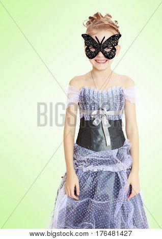 Slender little girl , with beautiful hair on her head, elegant long Princess dress. Posing in carnival mask.