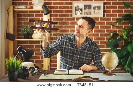 man with an airplane model a map and a globe dreams of traveling