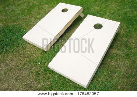 Wooden cornhole board beanbag toss game on green grass