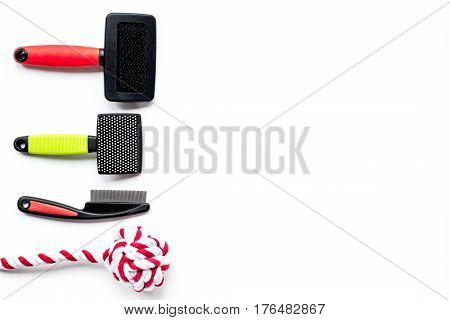 Pet care set with toys and grooming tools on white table background top view mockup