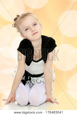 Beautiful little blonde girl dressed in a white short dress with black sleeves and a black belt.Girl sitting on the floor leaning on hands and smiling at the camera.