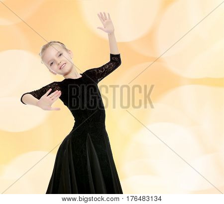 The slender little blonde girl dancer in the long dress of black color made specifically for performing .Girl graceful curves of the body.