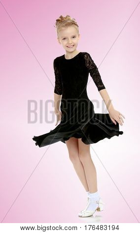 The slender little blonde girl dancer in the long dress of black color made specifically for performing .The girl gracefully spinning , the edges of her dress fluttering in the wind.