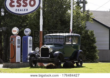 Antigonish, Nova Scotia, September 24, 2015 -- A gorgeous green model-T Ford sits beside two old Esso gas pumps with sheep lounging beside the car on a beautiful sunny afternoon in September