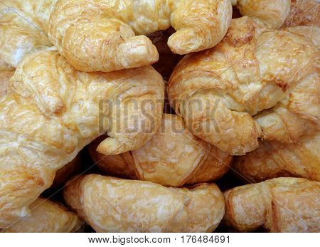 Pile of fresh croissant pastries at the bakery, for background