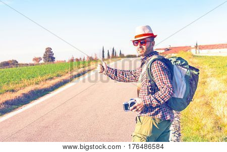 Traveler hitchhiker man thumb up walking on road - Middle age wanderer standing at county route on summer trip around world - Concept of cheap holidays with alternative ways to move