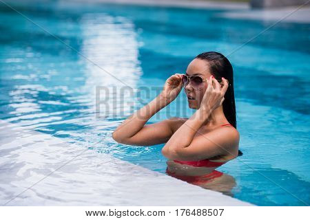 Woman wearing red swimsuit and sunglasses sitting in swimming pool.