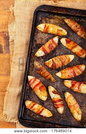 Homemade Bacon Wrapped Potatoes Wedges. Selective focus.