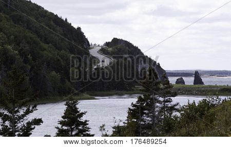 Wide view of the beautiful landscape with a car going down an