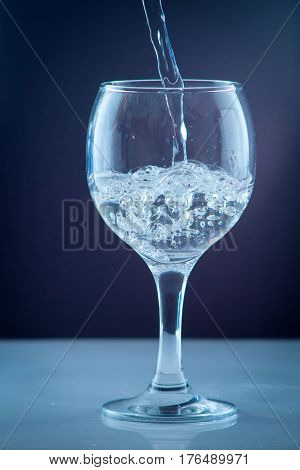Pure mineral water pouring from a bottle into a glass. bottle of clear drinking cold mineral water with gas in isolation on the background next to a glass transparent glass
